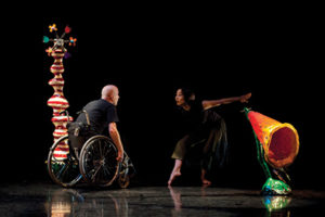 A photograph of two performers on a dark stage. They are interacting with each other. The performer on the right is a wheelchair user, the performer on the left is bending towards the left with their arms straight out behind their back
