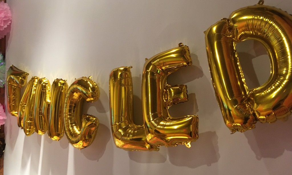 A photograph of gold balloons that spell Tangled hanging on a white wall. The photo is taken from below and to the right of the balloons looking upwards to the words.